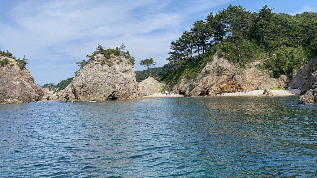 海岸で海水浴を楽しんでいる人たちが人たちが見える。